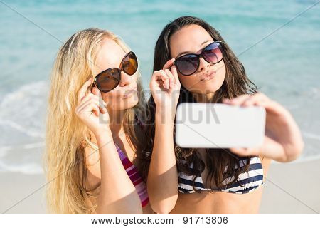 two friends in swimsuits taking a selfie at the beach