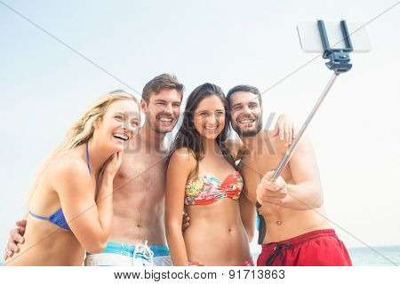 group of friends in swimsuits taking a selfie at the beach