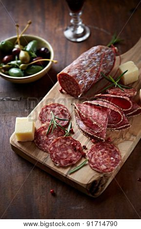 Sliced salami and hard cheese on a chopping board