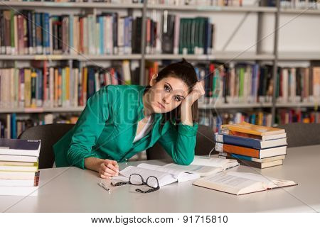 Confused Female Student Reading Many Books For Exam
