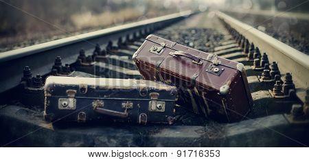 Two Vintage Suitcases Lie On Railway Tracks.