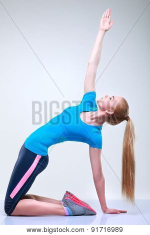 Beautiful  young girl is engaged in a fitness, on a light-grey background