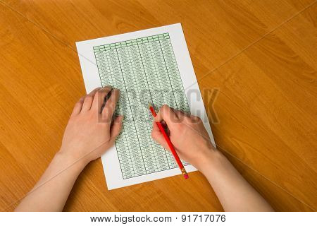 Hands holding pencil over documents