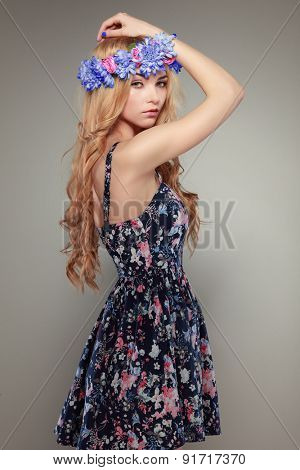 Beautiful sexual blonde in varicoloured clothes in a chaplet from flovers on a grey background