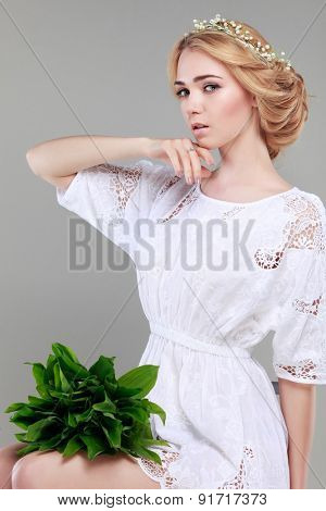 Beautiful sexual blonde  in white  clothes with the basket of flowers  on a grey background