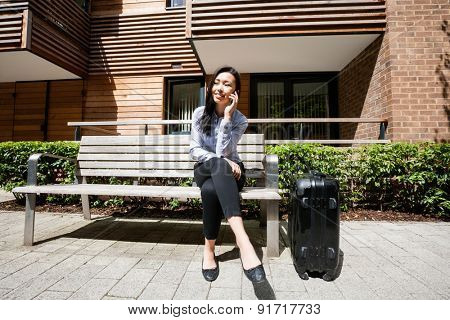 Full length of businesswoman answering cell phone while sitting by luggage on bench against building