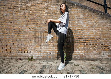 Full length side view of young fit woman stretching against brick wall