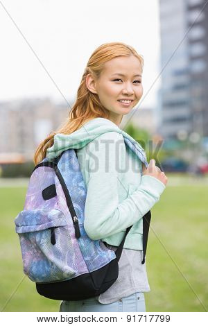 Portrait of happy young woman with backpack at college campus
