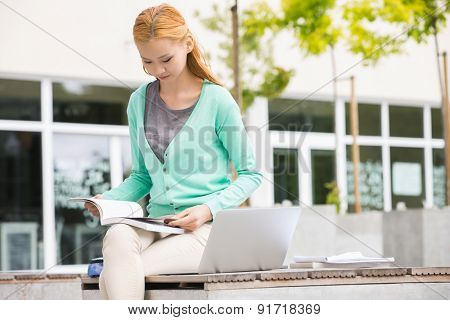 Young woman reading book at college campus