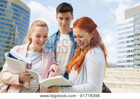 Happy young college students studying outdoors