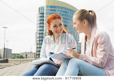 Smiling young university students studying against building