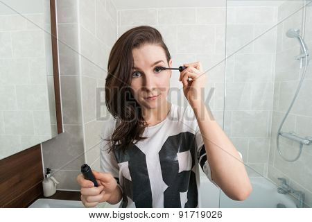 Portrait of beautiful woman applying mascara in bathroom