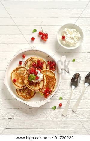 Pancakes With Cream And Red Currants In A Vintage Plate On A Light Wooden Surface
