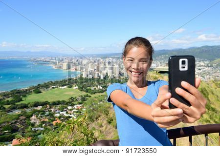 Hawaii tourist taking selfie photo of Honolulu and Waikiki beach using smartphone. Woman on hike visiting famous viewpoint lookout in Diamond Head State Monument and park, Oahu, Hawaii, USA.