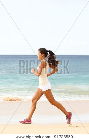 Female runner jogging during outdoor workout on beach. Mixed race Asian woman model training for marathon outdoor on beach sand. Healthy fit lifestyle.