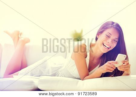 Smartphone woman using app on mobile cell phone smiling happy. Beautiful multicultural young woman model using smart phone texting sending text message lying on sofa. Mixed race Asian Caucasian girl.