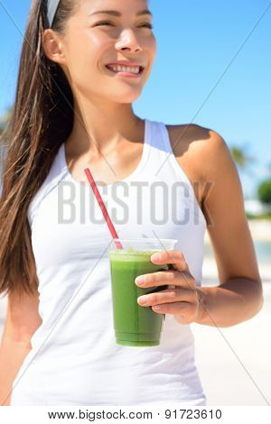 Green smoothie. Woman holding green vegetable detox juice outside in summer sun. Healthy lifestyle with beautiful mixed race Asian Caucasian female model taking a cleanse diet.
