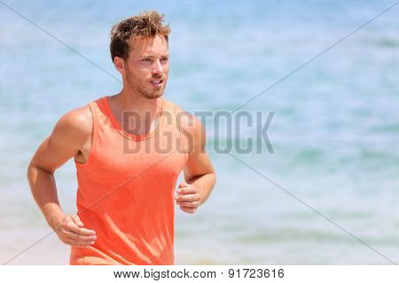 Athletic handsome young male running jogging fitness outside at beach in healthy lifestyle sun. Runner exercising healthy marathon training.