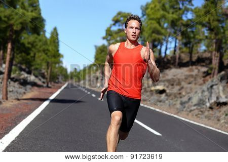 Sport sprinting young athlete handsome male training outdoors for marathon run. Fitness model in his twenties running on road in summer nature.