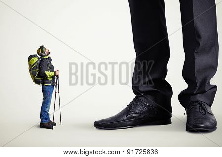 surprised hiker with backpack and hiking poles looking up with open mouth at big boss over light grey background