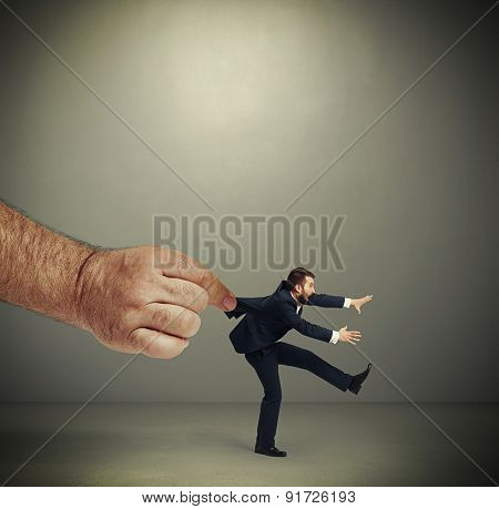 big mans hand kepping emotional running businessman over dark grey background