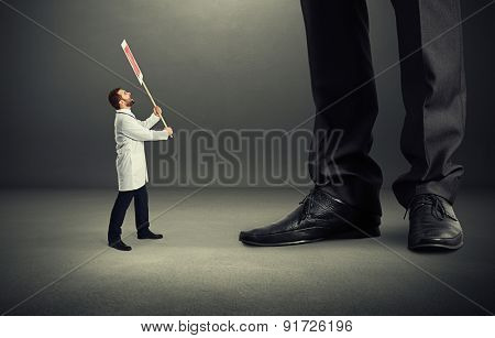 small screaming doctor holding placard and looking up at big legs over dark grey background