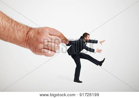 big hand stopping running man in formal wear over light grey background