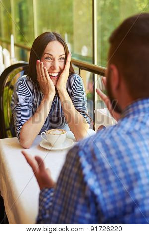happy loving couple on date at the restaurant. young excited woman laughing and looking at gesticulating man