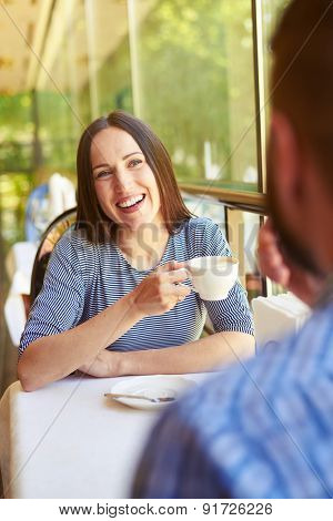 laughing woman holding cup of coffee and looking at man. loving couple on a date at cafe