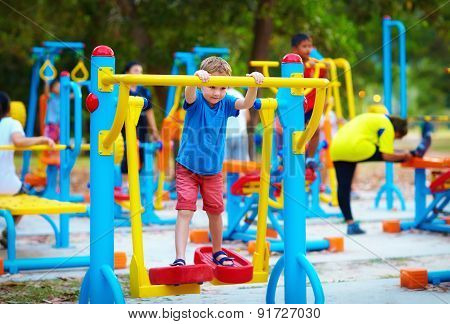 Cute Kid, Boy Exercising On Sport Ground With Other People On Background