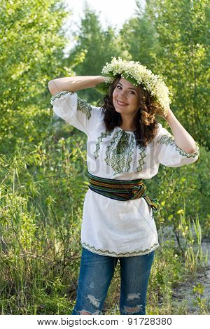 Portrait of a young beautiful in traditional Ukrainian embroidered shirt and a wreath of lilies of t
