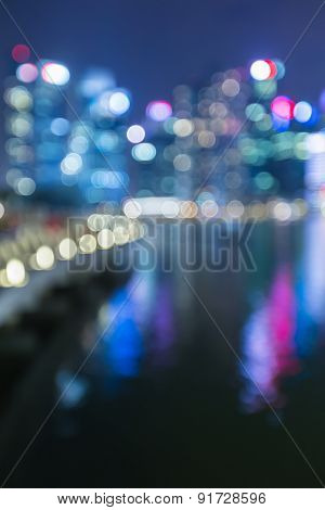 View of city night lights blurred bokeh background with water reflection