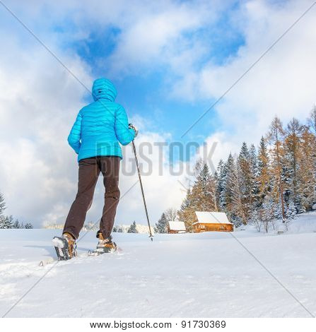 Young woman running with snowshoes on clear snow
