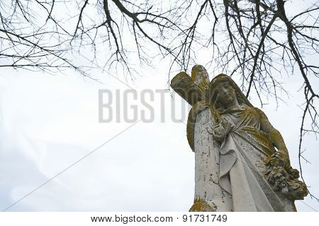 Female, stone cemetery statue leaning on cross and holding flower wreath