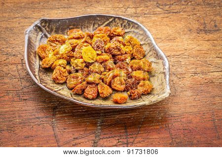dried goldenberries in a ceramic leaf shaped bowl against rustic scratched wood