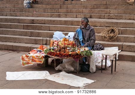 Indian Seller Sits On The Ghat Near Sacred River Ganges In Varanasi