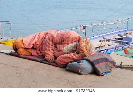 Indian Man Sleeps On The Ghat Near Sacred River Ganges In Varanasi