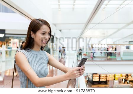 Asian woman reading something on mobile phone at shopping center