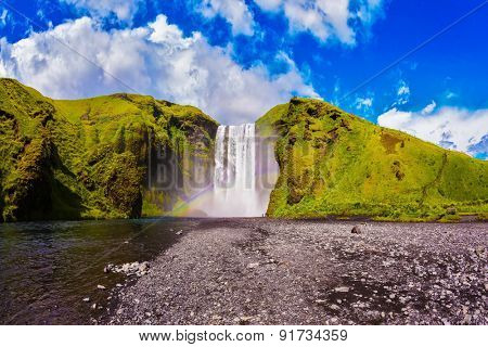 Iceland, waterfall Skogafoss summer, clouds of mist. Huge picturesque waterfall flowing from under a giant glacier