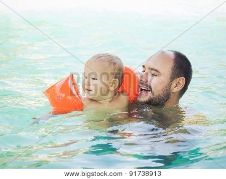 Baby and father in swimming pool