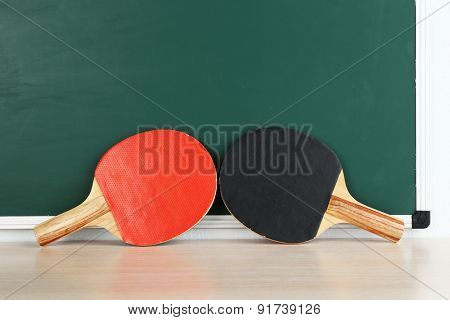 Table tennis rackets on blackboard background
