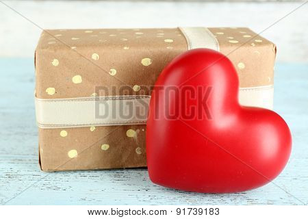 Red heart with present box on wooden table