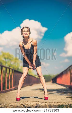 Pretty Woman In Short Black Dress On The Bridge