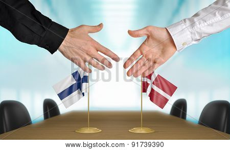 Finland and Denmark diplomats agreeing on a deal