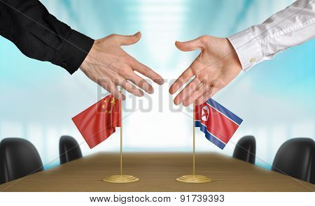 China and North Korea diplomats agreeing on a deal