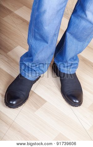 male legs in jeans and shoes in interere