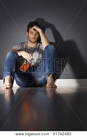Young man with bottle of whiskey sitting on floor, drinking.