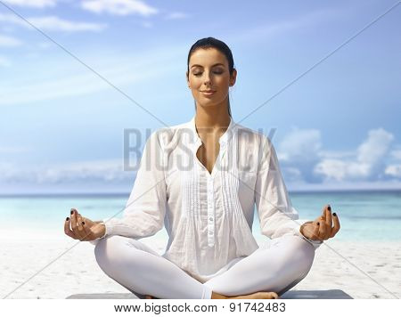 Young woman meditating eyes closed on the beach, smiling.