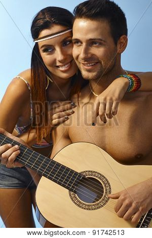 Summer portrait of happy loving couple embracing, man holding guitar.