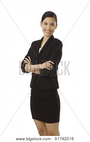 Happy young Asian woman standing arms crossed, smiling in black costume.